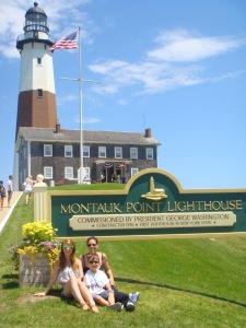 Family sitting on lawn next to welcome sign at Montauk Point lighthouse, Long Island, New York