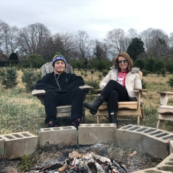 boy and a girl sitting in Adirondack chairs at a home made fire pit Santa's Christmas Tree Farm, Mattituck