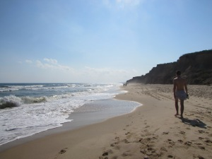 person walking along the shore at Ditch Plains beach, Montauk, New York