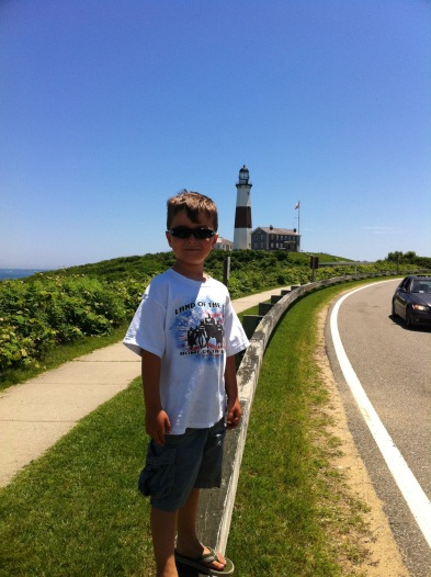 boy standing at road edge with Montauk lighthouse in foreground, Long Island, New York