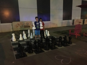 two boys playing giant chess on street of Niagara town, New York