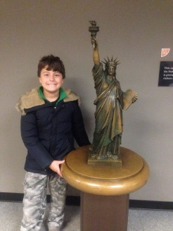 boy with a small bronze statue of Lady Liberty, Liberty Island, New York