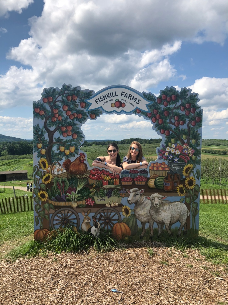 two women taking picture at photo stand for Fishkill Farm, New York