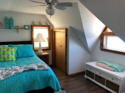 Bedroom in a tiny home with closet, storage, and full size bed