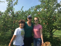 family smiling in orchard at Fishkill Farm, New York
