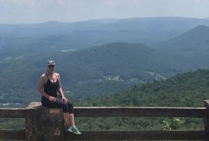 woman sitting on fence at Black Rock Mountain Overlook, Georgia