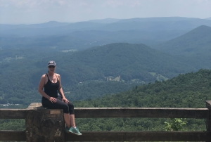 woman sitting on fence at Black Rock Mountain Overlook, Georgia