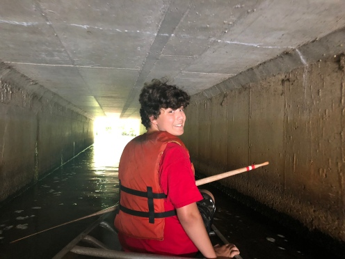 boy canoeing in tunnel, Peconic River, Long Island, New York