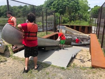 boys loading canoe on the ramp, Peconic River, Long Island, New York