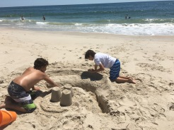 two boys making a sacn castle on the ocean beach at Sailor's Haven, Fire Island
