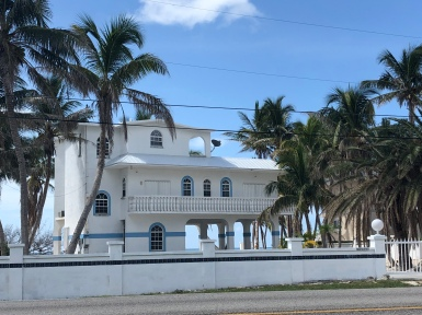 three-story white home with palm trees on the coast in the Florida Keys