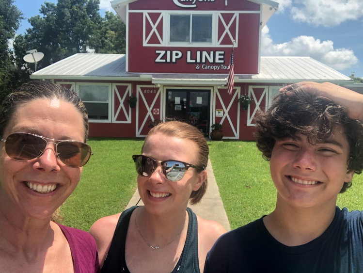 Family picture in front of red barn for Canyons Zip Line, Ocala, Florida