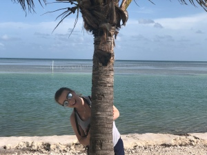 Girl peeking out from behind a palm tree, Florida Keys, Atlantic Ocean side