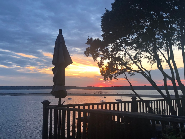 view of the sunset over Sand City and Hobart beach from a deck, Northport, New York