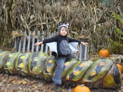Boy in a Bat costume on a giant man-made caterpillar at Roger Williams Zoo, Rhode Island
