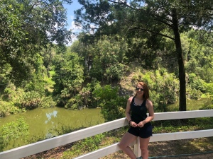Girl posing at Canyons Zip Lines, Ocala, Florida, with zip line and lake in the background
