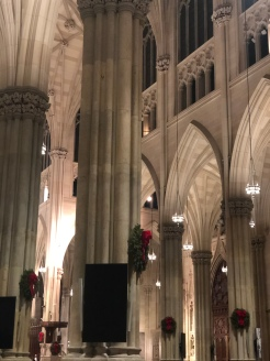 Inside St. Patrick's Cathedral, tall white marble columns with wreaths