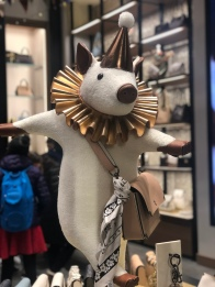 Merry Pig dancing with Coach purse holiday window display NYC