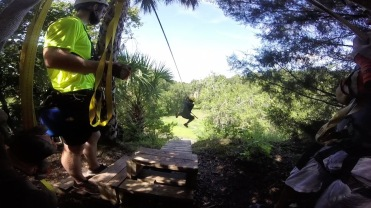 taking a running jump through the forest for the zip line at Canyons Zip Line,Ocala, Florida