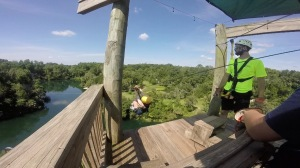 "Instructor with Girl jumping off the tower for the ""break out"" zip line over the canyon and lake at Canyons Zip Line, Ocala, Florida"