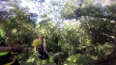 Instructor guiding girl to start the zip line at Canyons Zip Line , Ocala, Florida