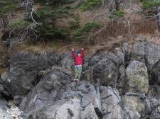 Victorious boy on a rocky climb at Acadia National Park, Maine