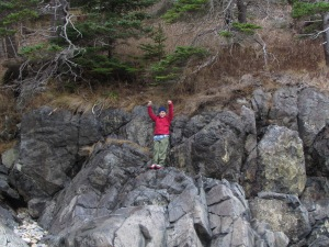 Victorious boy on a rocky climb at Acadia National Park, Maine