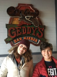 Kids pictured in front of Geddy's Restaurant sign in Bar Harbor, Maine