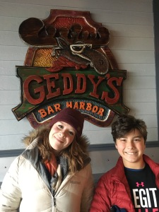 Kids pictured in front of the Geddy's Restaurant sign in Bar Harbor, Maine