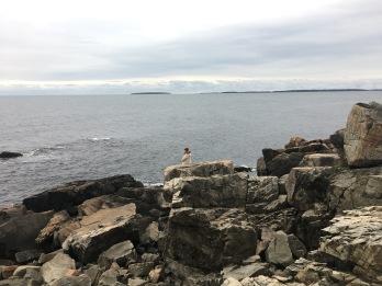 Woman standing edge rocky granite headlands, Acadia National Park, Maine