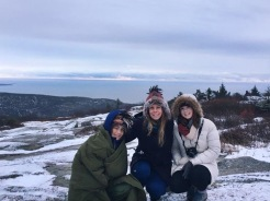 Family of three posing with the first sunrise on Cadillac Mountain in Acadia National Park, Maine, in winter