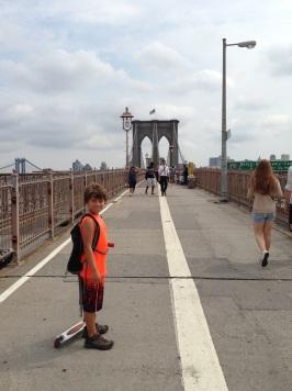 Boy with his scooter on the Brooklyn Bridge Pedestrian Walk