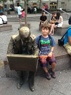 Bot sitting with Bronze Statue of a man with a briefcase, Double Check, in Zuccotti Park, NYC, as a symbol of September 11th