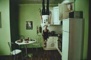 Woman upside down on the ceiling of her messy kitchen chaos