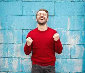 Man in a red sweatshirt expressing joy in front of a blue wall