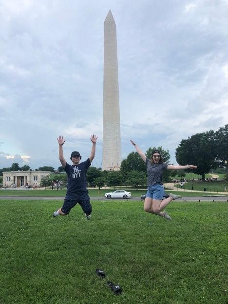 Two people jumping for joy in front of Washington Monument, D.C.