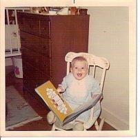 baby emilymaehood in rocking chair reading
