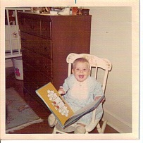 baby emilymaehood in rocking chair reading
