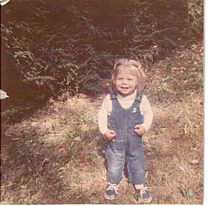 toddler emilymaehood in overalls in yard