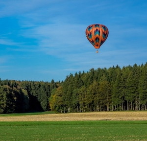hot air balloon over the forest clearing by blickpixel on pixabay.com