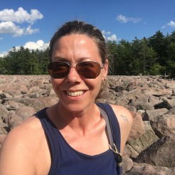 Woman posing at the boulder field with forest behind and blue skies at Hickory Run State Park, Pennsylvania