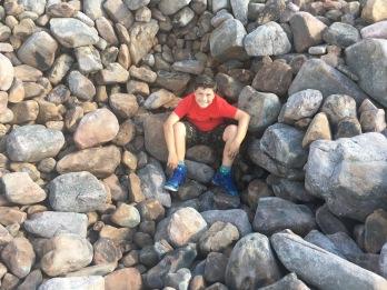 Boy sitting among rocks at boulder field, Hickory Run State Park, Pennsylvania
