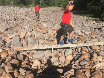 Two boys navigating across the boulder field at Hickory Run State Park, Pennsylvania