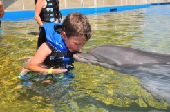 boy kissing bottlenose dolphin, Marineland, Florida