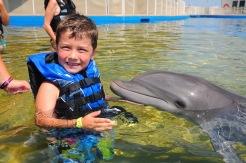 boy smiling with bottlenose dolphin, Marineland, Florida