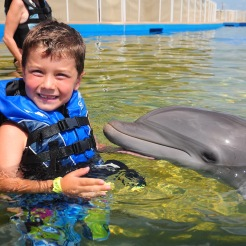 boy smiling with bottlenose dolphin, Marineland, Florida