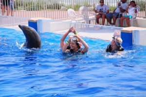 swimmers dansing with dolphins in oceanarium, Marineland, Florida
