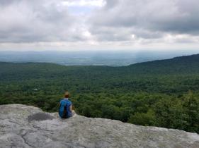 Woman sitting on edge overlook of Millbrook Mountain, Minnewaska Preserve, New York