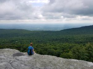 Woman sitting on edge overlook of Millbrook Mountain, Minnewaska Preserve, New York