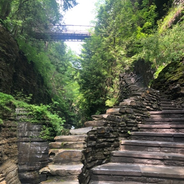 Looking up at the suspension bridge from the stone stairs at Watkins Glen State Park, New York
